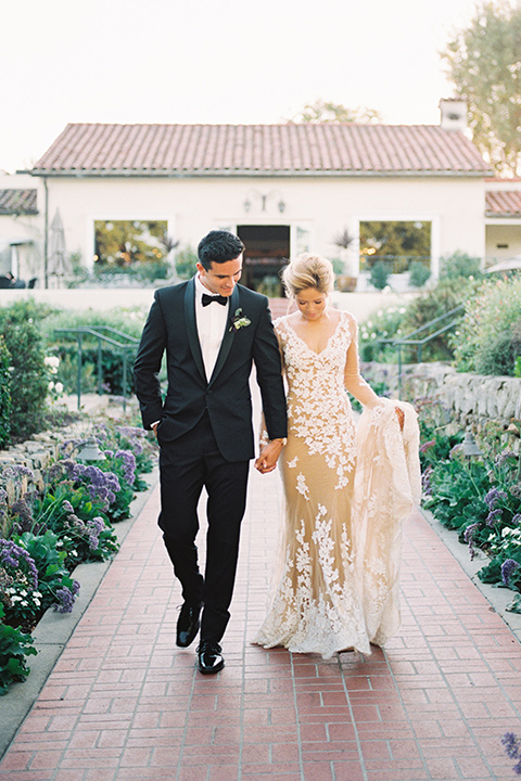 Inn-at-rancho-santa-fe-shoot--bride-and-groom-walking-bride-in-a-lace-gown-with-an-illusion-detailing-with-a-nude-underlay-with-her-hair-in-back-in-a-loose-bun-groom-in-a-black-tuxedo-with-black-blow-tie-and-a-white-and-black-olka-dot-pocket-square
