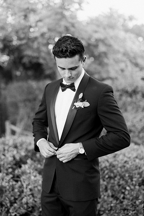 Inn-at-rancho-santa-fe-shoot-black-and-white-groom-fixing-coat-groom-in-a-black-tuxedo-with-black-blow-tie-and-a-white-and-black-olka-dot-pocket-square