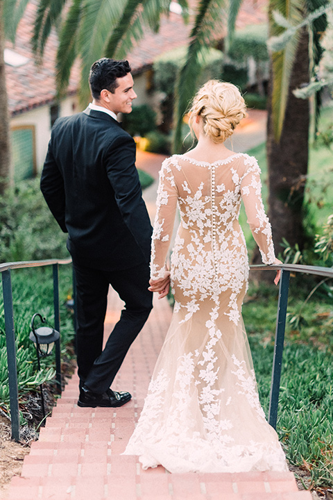 Inn-at-rancho-santa-fe-shoot-bride-and-groom-walking-down-the-stairs-bride-in-a-lace-gown-with-an-illusion-detailing-with-a-nude-underlay-with-her-hair-in-back-in-a-loose-bun-groom-in-a-black-tuxedo-with-black-blow-tie-and-a-white-and-black-olka-dot-pocket-square