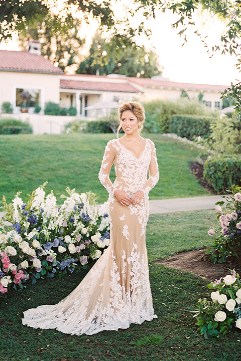 Inn-at-rancho-santa-fe-shoot-bride-full-length-looking-to-the-side-by-tree-bride-in-a-lace-gown-with-an-illusion-detailing-with-a-nude-underlay-with-her-hair-in-back-in-a-loose-bun