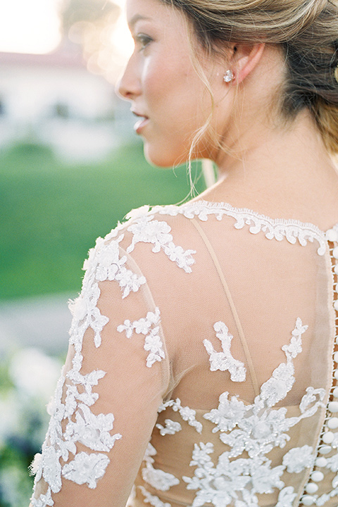 Inn-at-rancho-santa-fe-shoot-bride-looking-to-side-close-up-bride-in-a-lace-gown-with-an-illusion-detailing-with-a-nude-underlay-with-her-hair-in-back-in-a-loose-bun