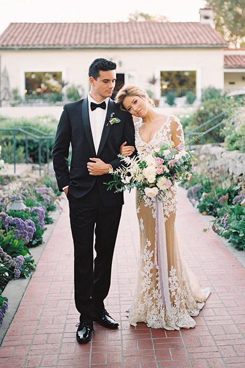 Inn-at-rancho-santa-fe-shoot-bride-with-head-resting-on-groom-groom-looking-down-bride-in-a-lace-gown-with-an-illusion-detailing-with-a-nude-underlay-with-her-hair-in-back-in-a-loose-bun-groom-in-a-black-tuxedo-with-black-blow-tie-and-a-white-and-black-olka-dot-pocket-square
