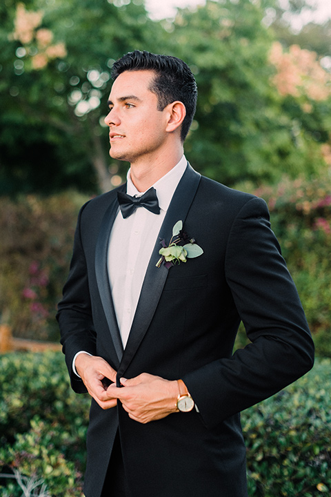Inn-at-rancho-santa-fe-shoot-groom-looking-to-the-side-buttoning-jacket-groom-in-a-black-tuxedo-with-black-blow-tie-and-a-white-and-black-olka-dot-pocket-square