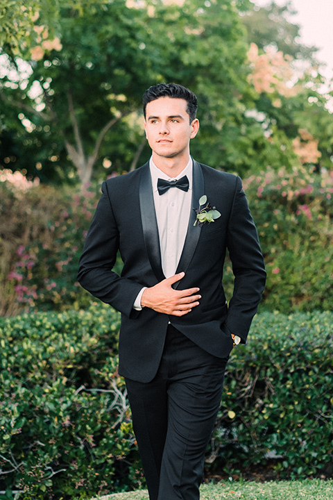 Inn-at-rancho-santa-fe-shoot-groom-walking-towards-camera-groom-in-a-black-tuxedo-with-black-blow-tie-and-a-white-and-black-olka-dot-pocket-square