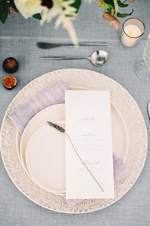 Inn-at-rancho-santa-fe-shoot-place-setting-white-plates-on-silver-chargers-with-white-menue-cardds-and-twigs-of-lavander-and-metallic-silverware