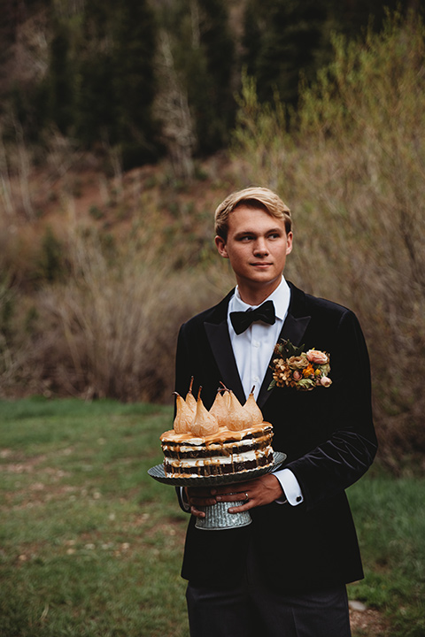 Utah-elopement-shoot--groom-holding-cake-groom-is-wearing-a-black-velvet-jacket-with-tuxedo-pants-and-a-simple-black-bow-tie