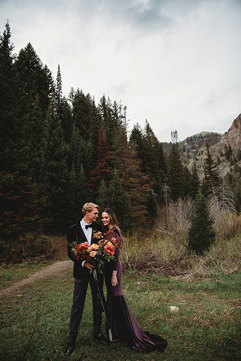 Utah-elopement-shoot-bride-and-groom-holding-each-other-bride-in-a-deep-plum-velvet-dress-with-long-sleeves-and-lace-detailing-on-the-bodice-the-groom-is-wearing-a-black-velvet-jacket-with-tuxedo-pants-and-a-simple-black-bow-tie