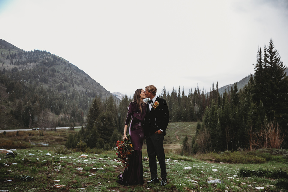 Utah-elopement-shoot-bride-and-groom-kiss-in-the-rain-with-mountains-behind-them-bride-in-a-deep-plum-velvet-dress-with-long-sleeves-and-lace-detailing-on-the-bodice-the-groom-is-wearing-a-black-velvet-jacket-with-tuxedo-pants-and-a-simple-black-bow-tie
