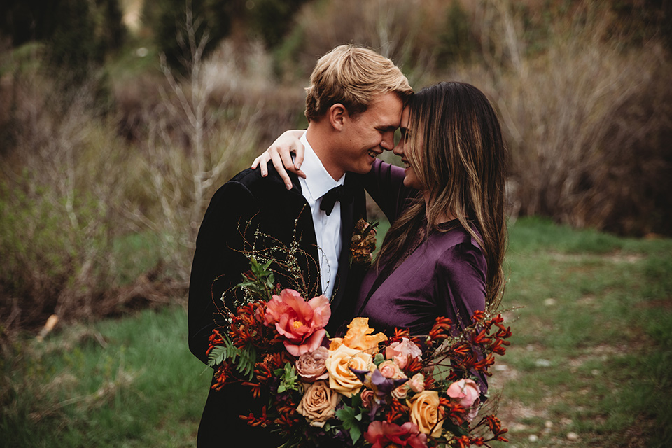 Utah-elopement-shoot-bride-and-groom-laughing-close-up-bride-in-a-deep-plum-velvet-dress-with-long-sleeves-and-lace-detailing-on-the-bodice-the-groom-is-wearing-a-black-velvet-jacket-with-tuxedo-pants-and-a-simple-black-bow-tie