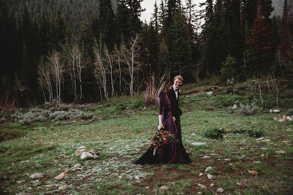 Utah-elopement-shoot-bride-and-groom-walking-across-the-frame-bride-in-a-deep-plum-velvet-dress-with-long-sleeves-and-lace-detailing-on-the-bodice-the-groom-is-wearing-a-black-velvet-jacket-with-tuxedo-pants-and-a-simple-black-bow-tie