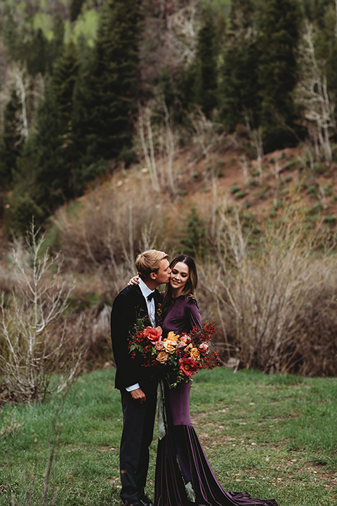 Utah-elopement-shoot-bride-holding-flowers-groom-kissing-her-on-the-cheek-bride-in-a-deep-plum-velvet-dress-with-long-sleeves-and-lace-detailing-on-the-bodice-the-groom-is-wearing-a-black-velvet-jacket-with-tuxedo-pants-and-a-simple-black-bow-tie