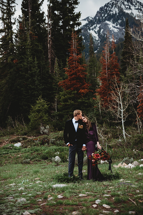 Utah-elopement-shoot-bride-resting-her-head-on-groom-groom-kissing-her-head-bride-in-a-deep-plum-velvet-dress-with-long-sleeves-and-lace-detailing-on-the-bodice-the-groom-is-wearing-a-black-velvet-jacket-with-tuxedo-pants-and-a-simple-black-bow-tie
