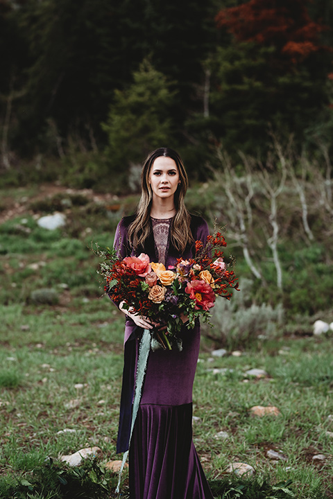 Utah-elopement-shoot-bride-straight-on-looking-at-camera-holding-flowers-bride-in-a-deep-plum-velvet-dress-with-long-sleeves-and-lace-detailing-on-the