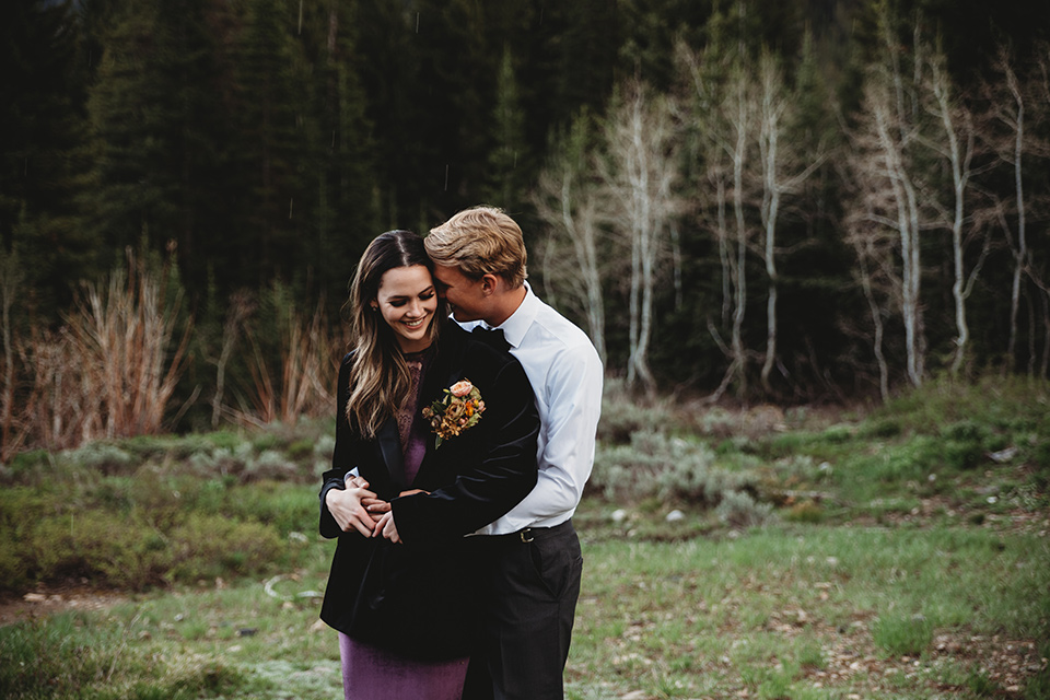 Utah-elopement-shoot-bride-wearing-groom-jacket-while-he-holds-her-bride-in-a-deep-plum-velvet-dress-with-long-sleeves-and-lace-detailing-on-the-bodice-the-groom-is-wearing-a-black-velvet-jacket-with-tuxedo-pants-and-a-simple-black-bow-tie
