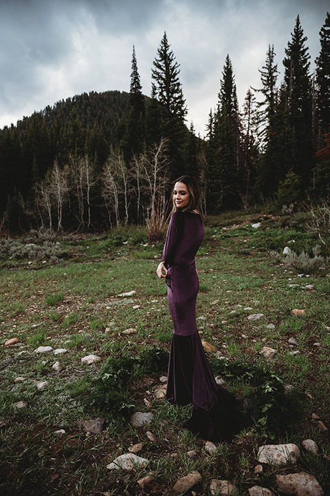 Utah-elopement-shoot-bride-with0her-back-turned-to-the-camera-looking-over-her-shoulder-bride-in-a-deep-plum-velvet-dress-with-long-sleeves-and-lace-detailing-on-the