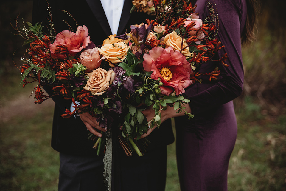 Utah-elopement-shoot-florals-close-up-bride-in-a-deep-plum-velvet-dress-with-long-sleeves-and-lace-detailing-on-the-bodice-the-groom-is-wearing-a-black-velvet-jacket-with-tuxedo-pants-and-a-simple-black-bow-tie
