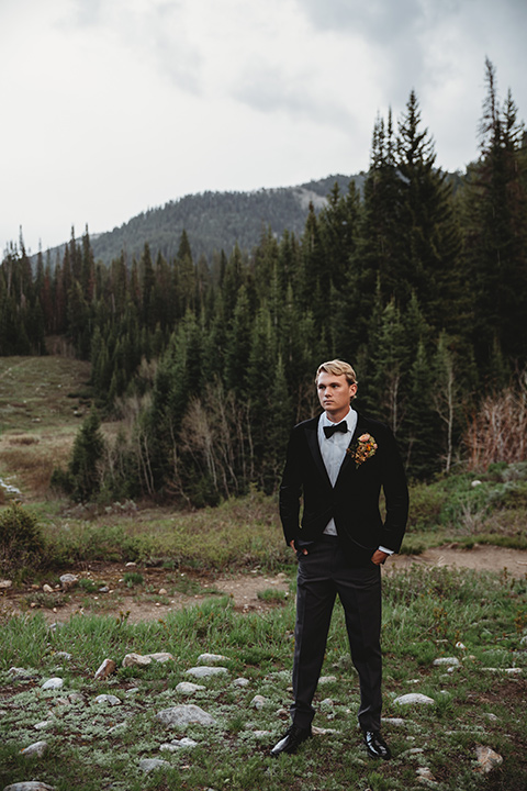 Utah-elopement-shoot-groom-standing-with-hands-in-his-pockets-groom-holding-cake-groom-is-wearing-a-black-velvet-jacket-with-tuxedo-pants-and-a-simple-black-bow-tie