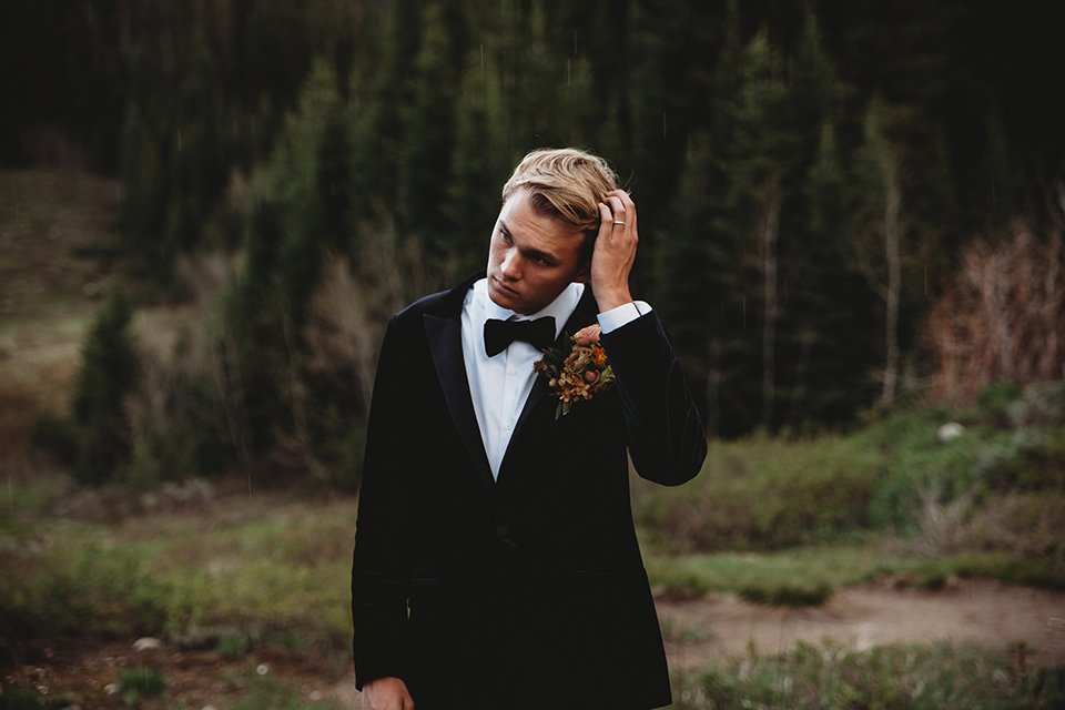 Utah-elopement-shoot-groom-touching-his-hair-groom-is-wearing-a-black-velvet-jacket-with-tuxedo-pants-and-a-simple-black-bow-tie