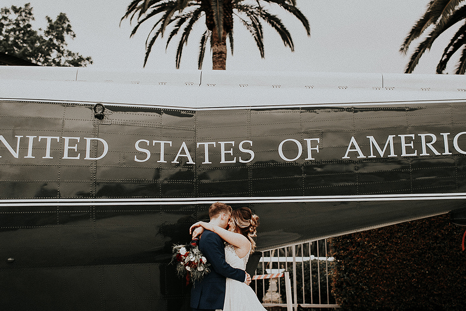 Orange-county-elegant-wedding-shoot-at-the-nixon-library-bride-and-groom-hugging-with-bouquet