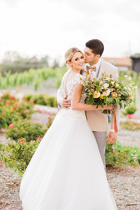 Temecula-outdoor-wedding-at-avensole-winery-bride-and-groom-kissing-and-hugging