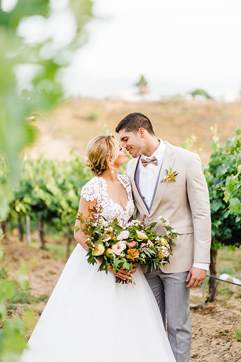 Temecula-outdoor-wedding-at-avensole-winery-bride-and-groom-kissing