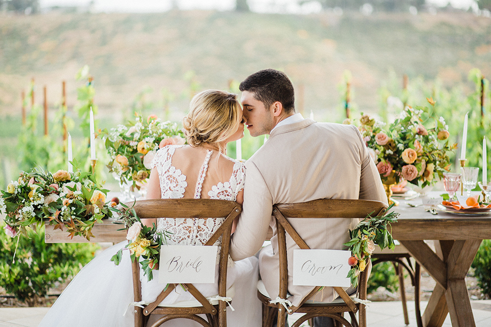 Temecula-outdoor-wedding-at-avensole-winery-bride-and-groom-sitting-at-table-kissing