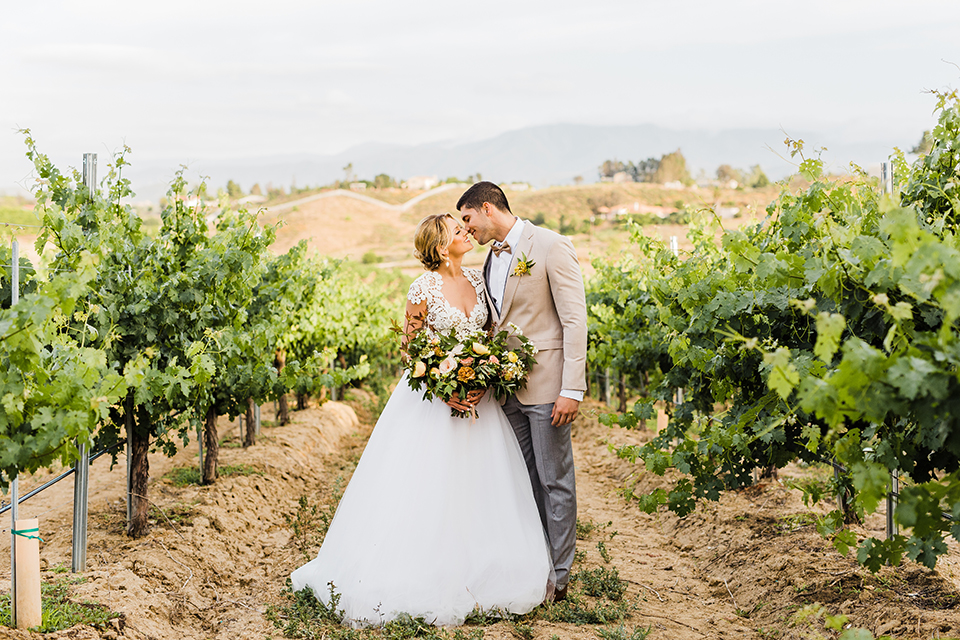 Temecula-outdoor-wedding-at-avensole-winery-bride-and-groom-standing-and-kissing