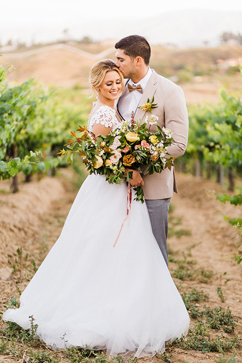 Temecula-outdoor-wedding-at-avensole-winery-bride-and-groom-standing-kissing