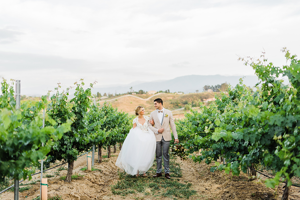 Temecula-outdoor-wedding-at-avensole-winery-bride-and-groom-walking-and-holding-hands