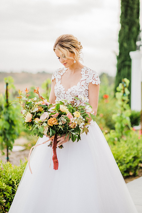 Temecula-outdoor-wedding-at-avensole-winery-bride-holding-bouquet