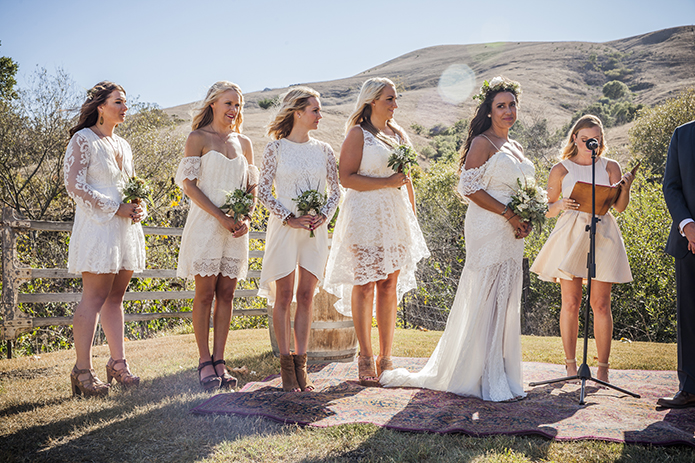 Rustic-barn-outdoor-wedding-bride-and-bridesmaids-standing-during-ceremony