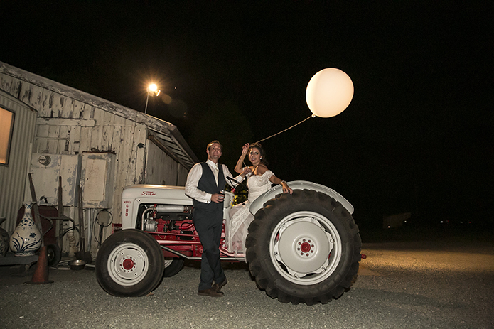 Rustic-barn-outdoor-wedding-bride-and-groom-by-tractor-holding-white-balloon