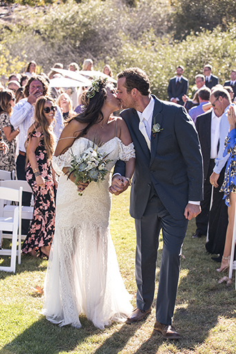 Rustic-barn-outdoor-wedding-bride-and-groom-kissing-at-the-end-of-the-aisle-after-ceremony