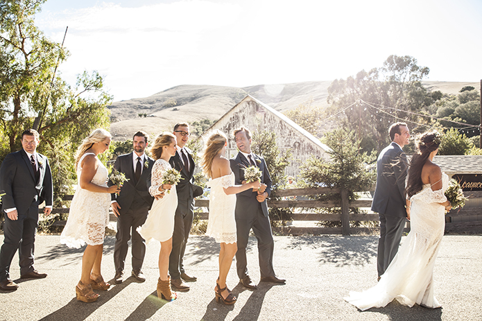 Rustic-barn-outdoor-wedding-bride-and-groom-walking-with-wedding-party