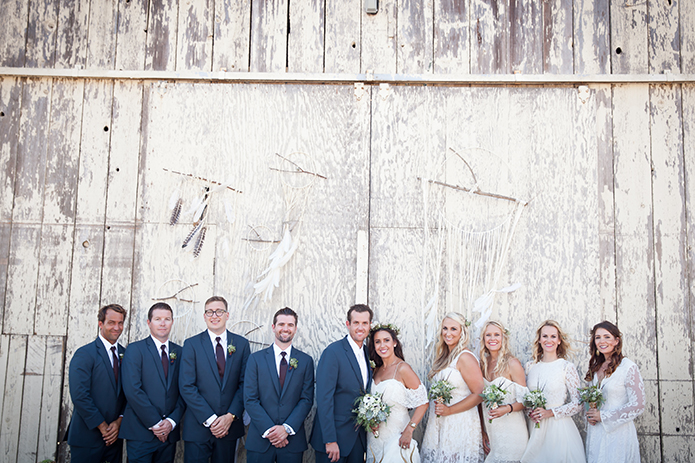 Rustic-barn-outdoor-wedding-bride-and-groom-with-wedding-party-outside-bar
