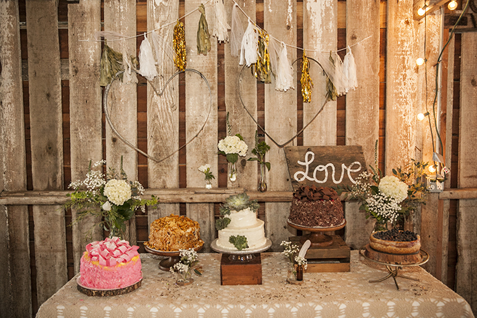 Rustic-barn-outdoor-wedding-dessert-table-with-assortment-of-desserts-with-love-sign