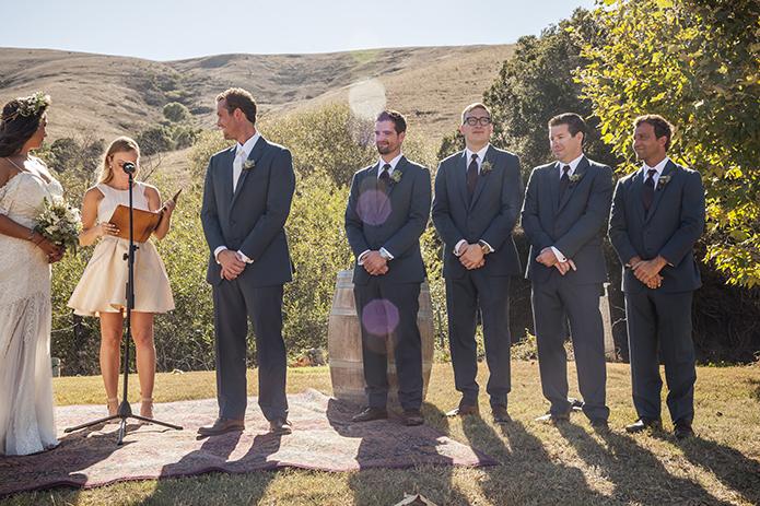 Rustic-barn-outdoor-wedding-groom-and-groomsmen-standing-during-ceremony