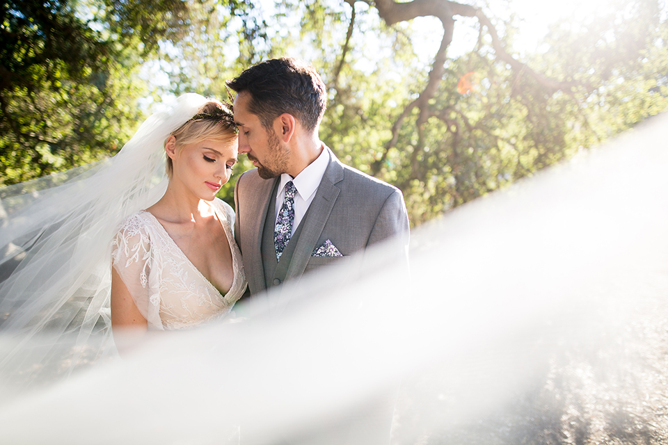 Bohemian-outdoor-wedding-shoot-bride-and-groom-hugging-with-veil