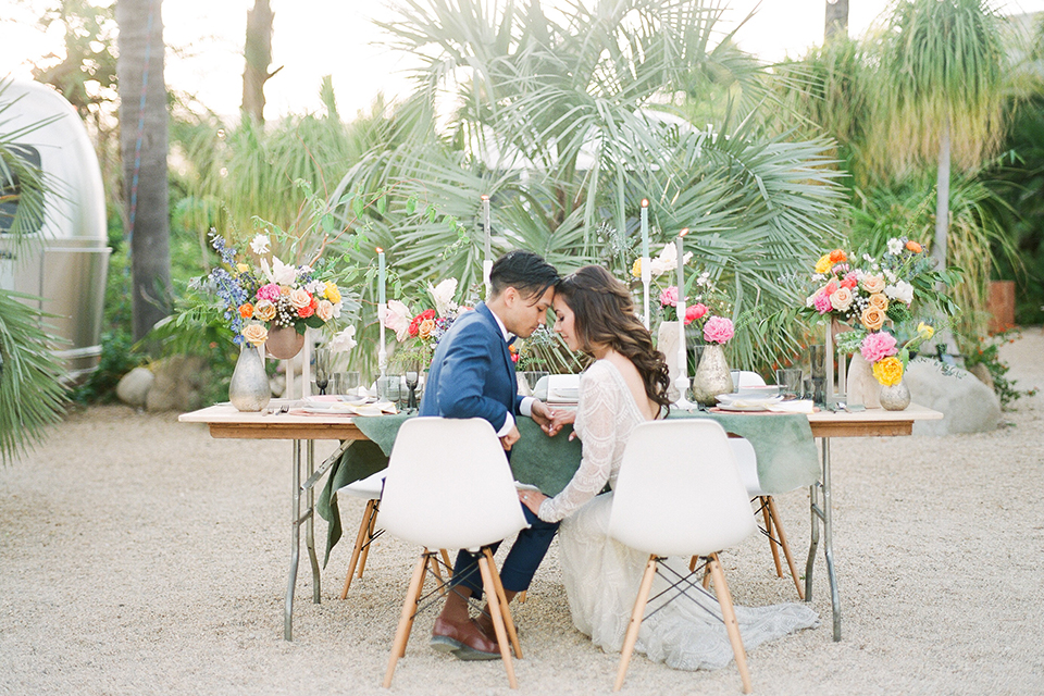 Caravan-outpost-outdoor-wedding-shoot-bride-and-groom-sitting-at-table-hugging