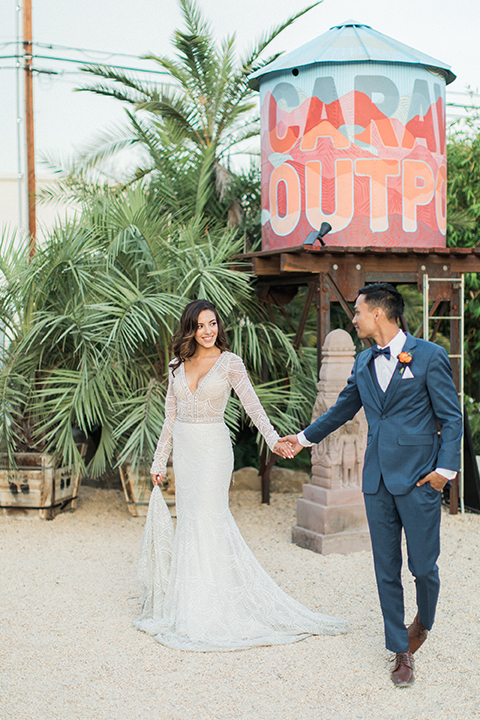 Caravan-outpost-outdoor-wedding-shoot-bride-and-groom-standing-holding-hands-by-outpost