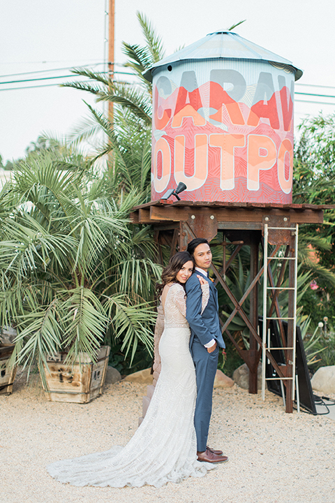 Caravan-outpost-outdoor-wedding-shoot-bride-and-groom-standing-hugging-by-outpost