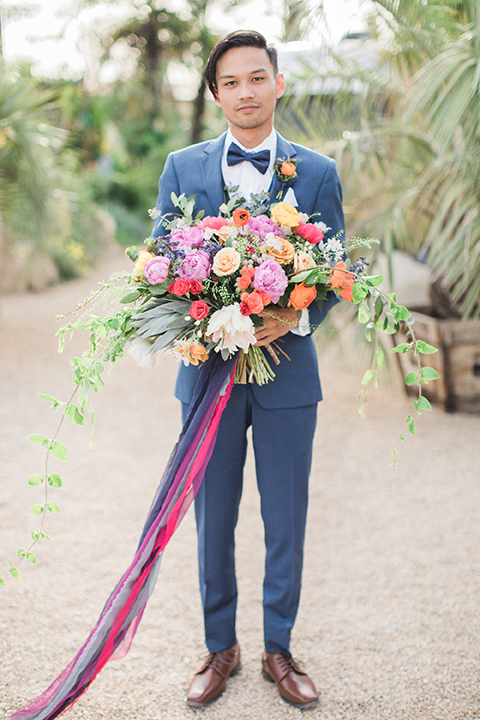 Caravan-outpost-outdoor-wedding-shoot-groom-blue-suit-holding-bouquet