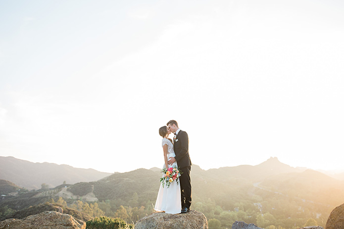 Cielo-Farms-Wedding-Couple-Standing-on-Rock-Kissing