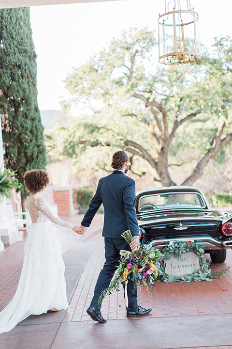 Colorful-bohemian-wedding-shoot-bride-and-groom-holding-hands-and-walking
