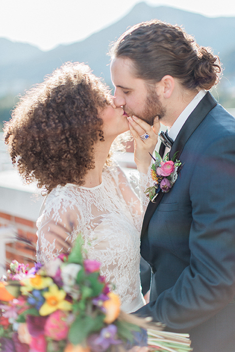 Colorful-bohemian-wedding-shoot-bride-and-groom-standing-kissing
