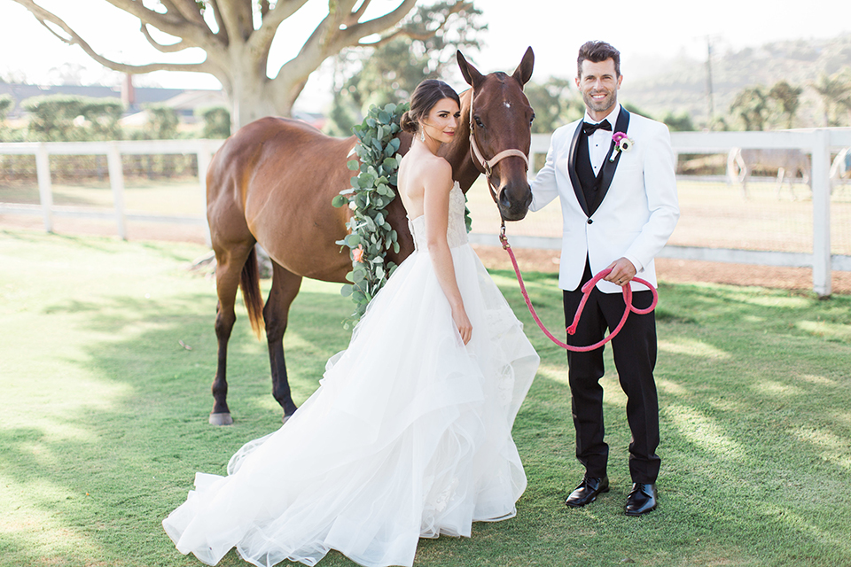 Santa-barbara-outdoor-wedding-bride-and-groom-standing-by-horse-smiling