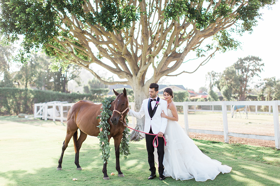 Santa-barbara-outdoor-wedding-bride-and-groom-standing-by-horse-with-flowers
