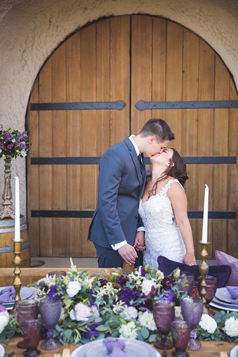 Santa-barbara-wedding-shoot-at-cottonwood-canyon-winery-bride-and-groom-standing-by-cake-kissing