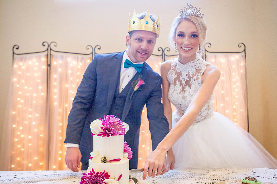 Fit-for-royalty-wedding-shoot-bride-and-groom-cutting-cake