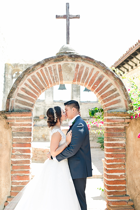 San-juan-capistrano-wedding-shoot-at-franciscan-gardens-bride-and-groom-standing-kissing-under-arch